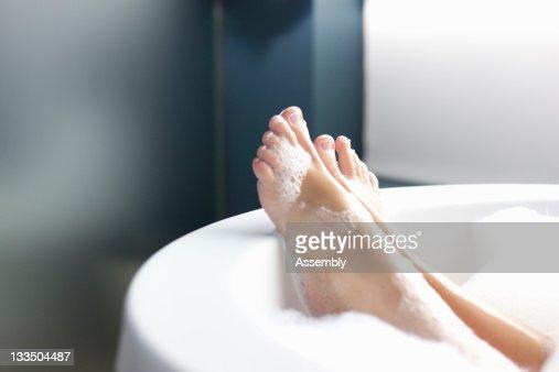 Feet of woman relaxing in bubble bath