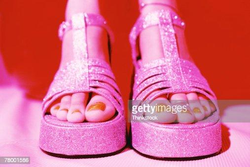 Feet of woman wearing glittery platform sandals