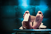 Grungy photo of feet with toe tag on a morgue tableGrungy photo of feet with toe tag on a morgue table