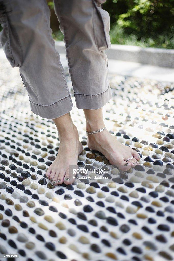 Feet on a pebble floor outdoors : Stock Photo