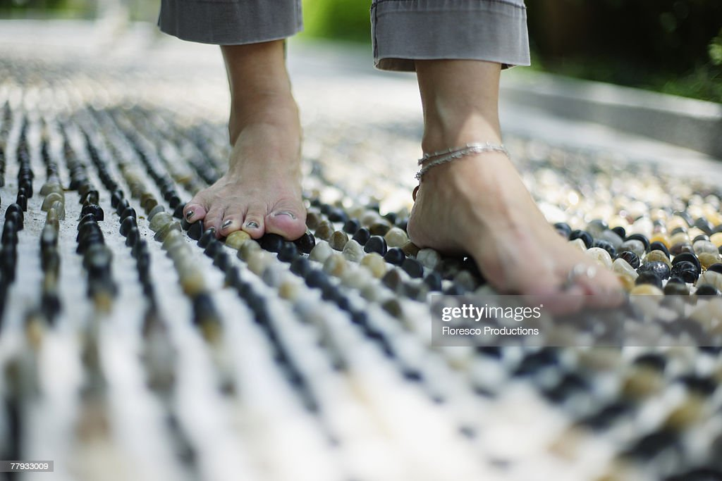 Feet on a pebble floor outdoors : Stock Photo