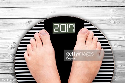 2017 feet on a weight scale, white wooden floor background : Stock Photo