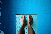 looking down on feet on diving board over pool