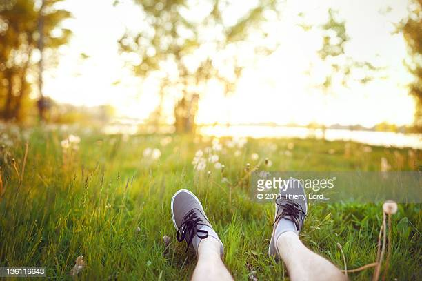 Feet on grass and sunset in background