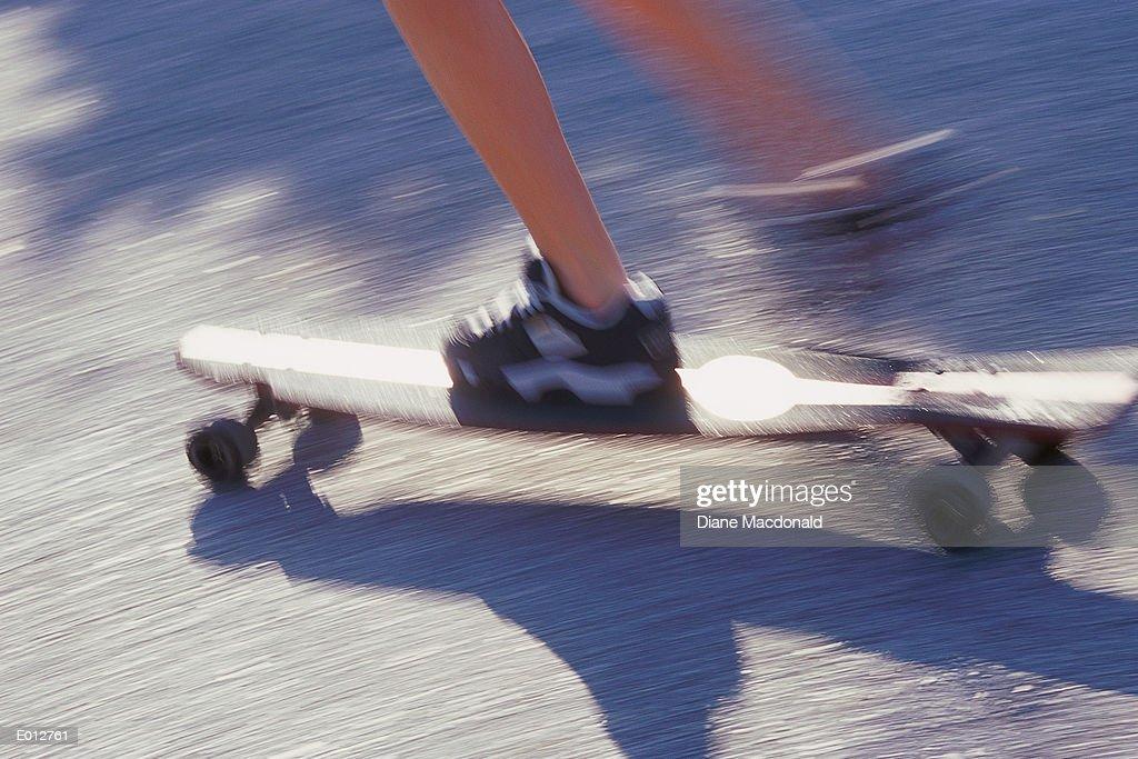 Feet on moving skateboard : Stock Photo