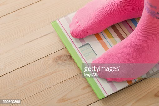 Feet on scales on wooden floor : Stock Photo