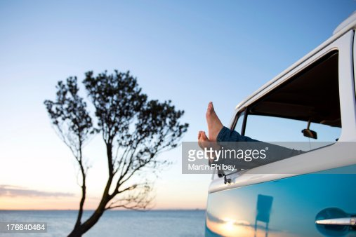 Feet out of camper van window at dusk : Stock Photo