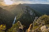 Hiking boots over the edge looking out over a series of cliffs with the sun light beaming through