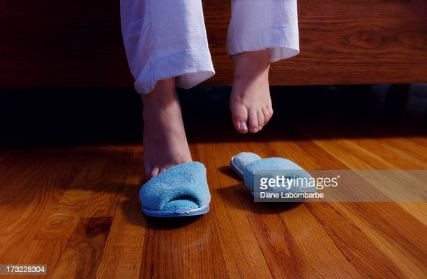 Feet Slipping Into Slippers In A Dark Bedroom