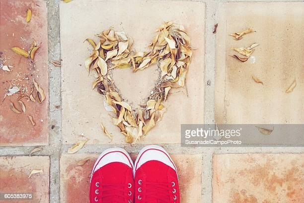 Feet standing in front of heart shape made of leaves