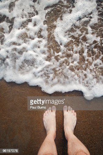 Feet standing on beach and waves lapping on shore : Stock Photo