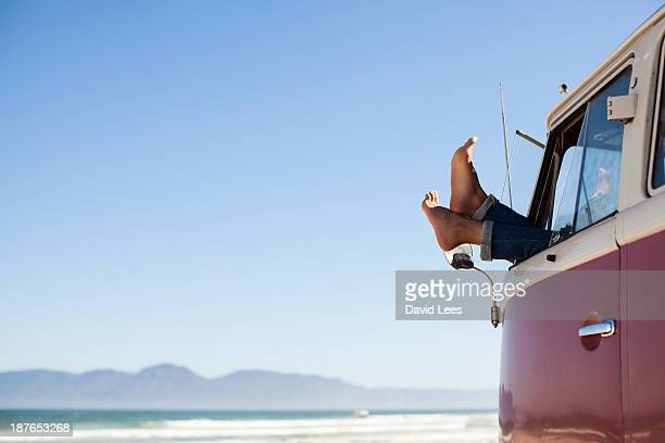 Feet sticking out of camper van window at beach