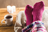Pair of feet in warm, woolly socks relaxing on a cushion with mug of tea and candles nearby.