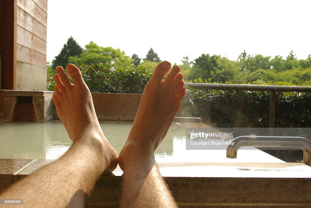 Feet up on stone bathtub : Stock Photo