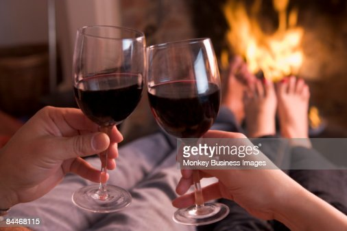 Feet warming at fireplace with hands holding wine : Stock Photo