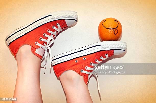 Feet wearing orange sneakers balancing an orange