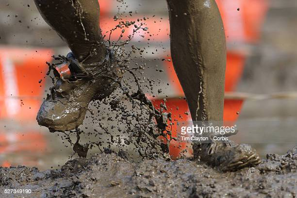 Feet with mud flying as competitors emerge from the mud pit during the New York Merrell Down and Dirty Obstacle Race presented by Subaru Over 6000...