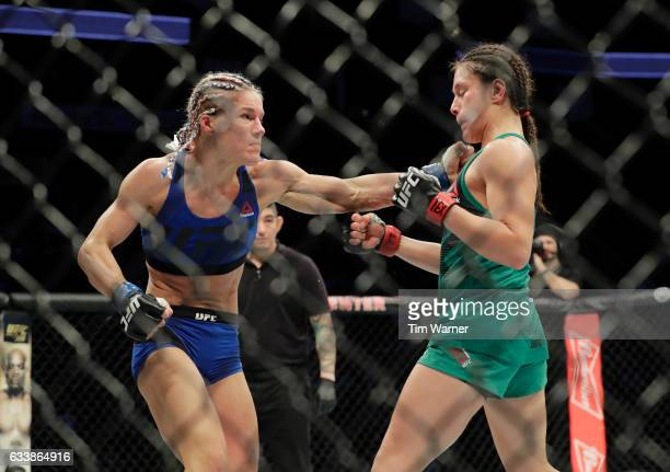 Felice Herrig hits Alexa Grasso of Mexico with a left hook in the third round of their women's strawweight bout during the UFC Fight Night event at...