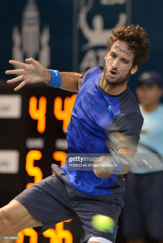 Feliciano Lopez of Spain hits the ball as return to Go Soeda of Japan during the second round of Tennis ATP Thailand Open 2013 tournament in Bangkok on September 25, 2013. AFP PHOTO / PORNCHAI KITTIWONGSAKUL