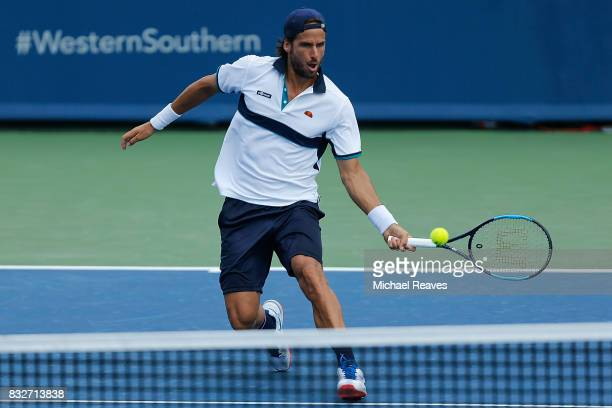 Feliciano Lopez of Spain returns a shot to Grigor Dimitrov of Bulgaria during Day 5 of the Western and Southern Open at the Lindner Family Tennis...