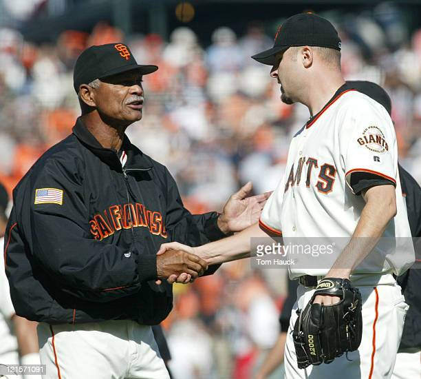 Felipe Alou Manager of the San Francisco Giants congratulates pitcher Jason Schmidt on his complete game after the NLDS Game 1 at Pac Bell Park in...
