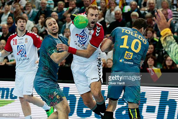 Felipe Borges and Jose Toledo of Brazil challenges for the ball with Davor Cutura of Serbia during the Handball Supercup between Brazil and Serbia on...