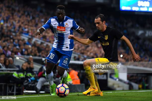 Felipe Caicedo of RCD Espanyol competes for the ball with Diego Godin of Club Atletico de Madrid during the La Liga match between RCD Espanyol and...
