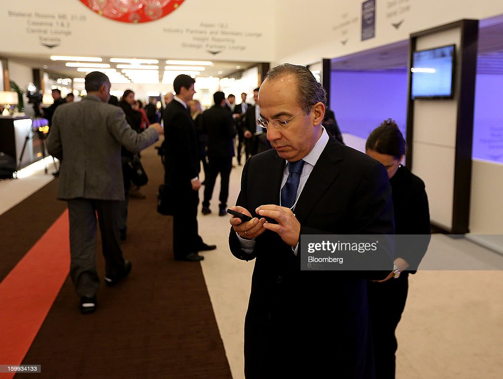 Felipe Calderon, former president of Mexico, checks his cell phone while in the halls on the opening day of the World Economic Forum (WEF) in Davos, Switzerland, on Wednesday, Jan. 23, 2013. World leaders, Influential executives, bankers and policy makers attend the 43rd annual meeting of the World Economic Forum in Davos, the five day event runs from Jan. 23-27. Photographer: Jason Alden/Bloomberg via Getty Images