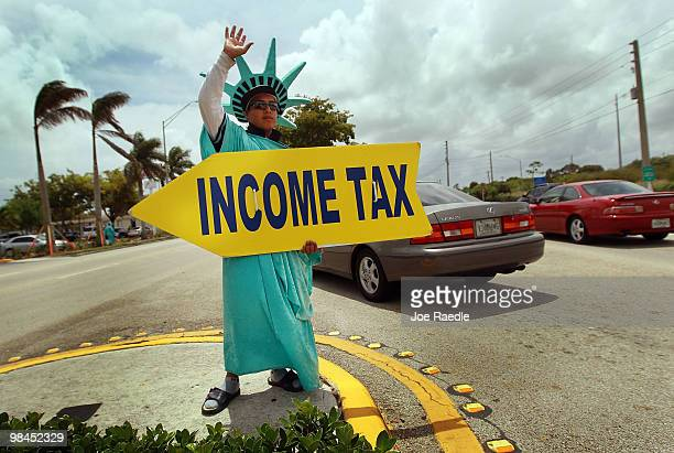 Felipe Castro holds a sign advertising a tax preparation office for people that still need help completing their taxes before the Internal Revenue...