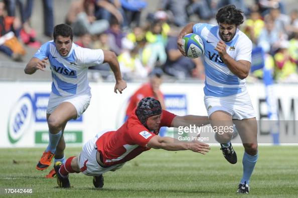 Felipe Ezcurra of Argentina evades a flying Sion Bennett of Wales during the 2013 IRB Junior World Championship match between Wales and Argentina at...