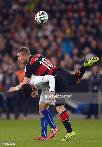 Felipe Guitierrez of Chile is challenged by Lukas Podolski of Germany during the International Friendly match between Germany and Chile at...