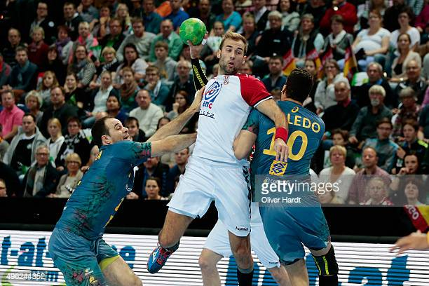 Felipe Henrique Teixeira and Jose Toledo of Brazil challenges for the ball with Davor Cutura of Serbia during the Handball Supercup between Brazil...