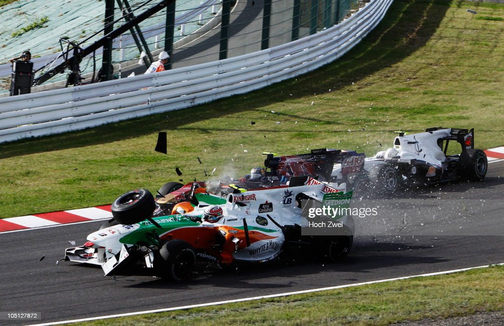 Felipe Massa (red) of Brazil and Ferrari and Vitantonio Liuzzi (white) of Italy and Force India crash at the first corner at the start of the Japanese Formula One Grand Prix at Suzuka Circuit on October 10, 2010 in Suzuka, Japan.
