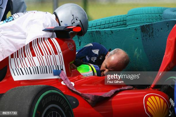 Felipe Massa of Brazil and Ferrari is attended to by FIA doctor Gary Hartstein medical staff and marshalls following his accident during qualifying...