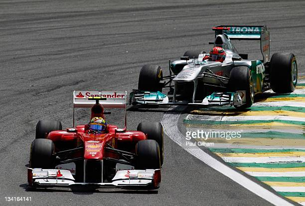 Felipe Massa of Brazil and Ferrari leads from Michael Schumacher of Germany and Mercedes GP during the Brazilian Formula One Grand Prix at the...