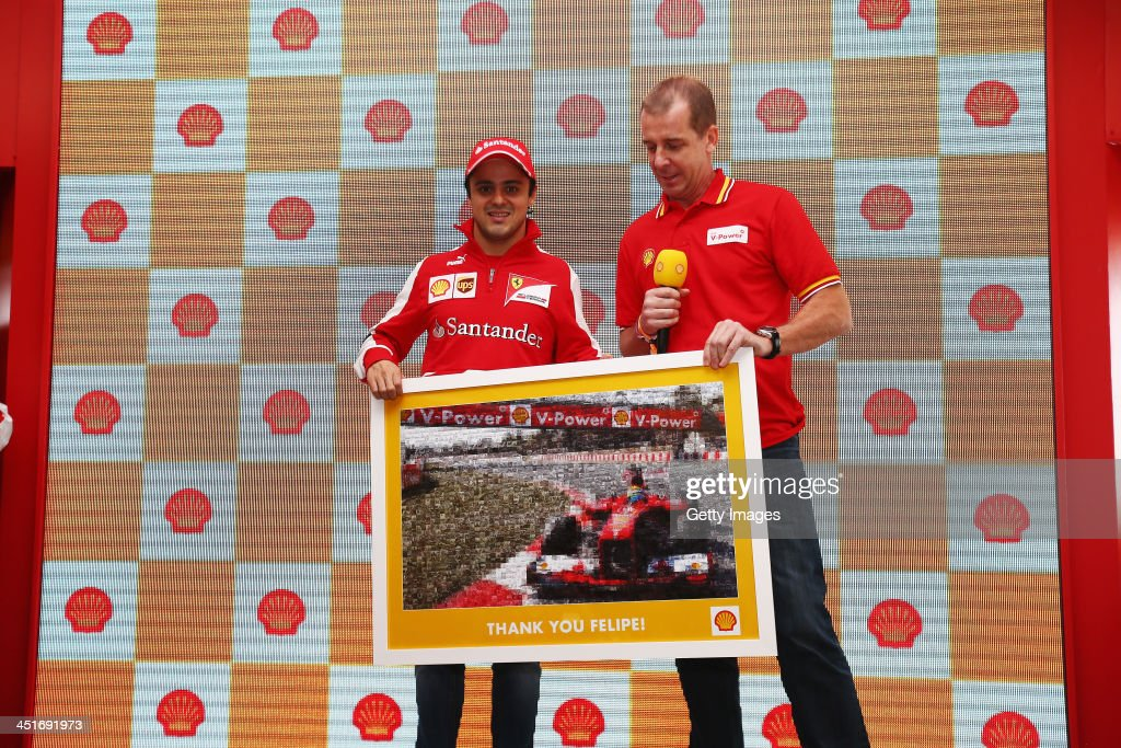 Felipe Massa of Brazil and Ferrari receives a picture of himself from Shell while making a guest appearance in their suite before the Brazilian...