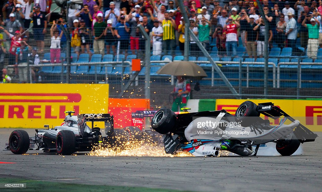 <a gi-track='captionPersonalityLinkClicked' href=/galleries/search?phrase=Felipe+Massa&family=editorial&specificpeople=206660 ng-click='$event.stopPropagation()'>Felipe Massa</a> of Brazil and Williams crashes with <a gi-track='captionPersonalityLinkClicked' href=/galleries/search?phrase=Kevin+Magnussen&family=editorial&specificpeople=7882003 ng-click='$event.stopPropagation()'>Kevin Magnussen</a> of Denmark and McLaren Mercedes as <a gi-track='captionPersonalityLinkClicked' href=/galleries/search?phrase=Daniel+Ricciardo&family=editorial&specificpeople=6547569 ng-click='$event.stopPropagation()'>Daniel Ricciardo</a> of Australia and Infiniti Red Bull Racing passes by during the German Formula One Grand Prix at Hockenheimring on July 20, 2014 in Hockenheim, Germany.