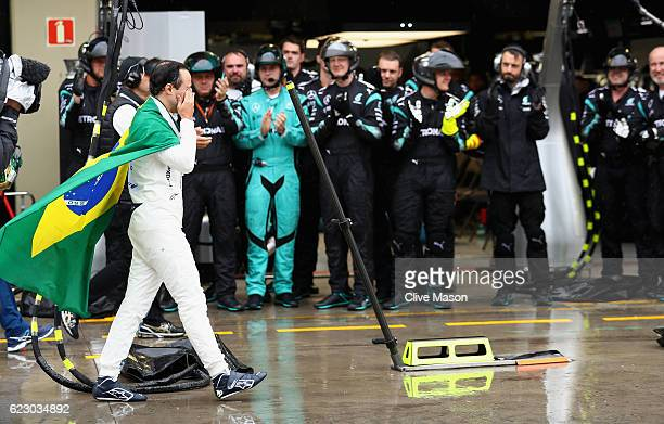Felipe Massa of Brazil and Williams cries walking down the pitlane after retiring from his final home grand prix the Mercedes team applaud him during...