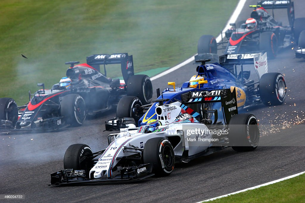 Felipe Massa of Brazil and Williams drives into the first corner with damage to his car during the Formula One Grand Prix of Japan at Suzuka Circuit...