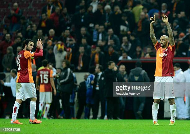 Felipe Melo and Selcuk Inan of Galatasaray greet supporters at the end of the UEFA Champions League round of 16 first leg soccer match between...