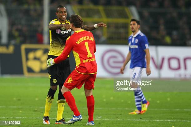 Felipe Santana and Roman Weidenfeller of Dortmund celebrate the 20 victory and Ciprian Marica of Schalke looks dejected after the Bundesliga match...