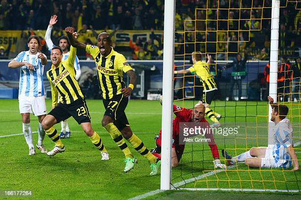 Felipe Santana of Borussia Dortmund celebrates scoring their third and winning goal with team mate Julian Schieber as goalkeeper Willy Caballero and...