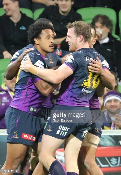 Felise Kaufusi of the Storm is congratulated by Tim Glasby and his teammates after scoring a try during the round 13 NRL match between the Melbourne...