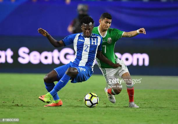 Felix Crisanto of Honduras battles for the ball with Orbelin Pineda of Mexico during the first half in a quarterfinal match during the CONCACAF Gold...