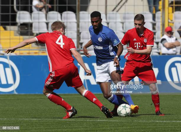 Felix Goetze and Niklas Tarnat of FC Bayern Muenchen fights for the ball with Haji Wright of FC Schalke 04 during the AJuniors semi final first leg...