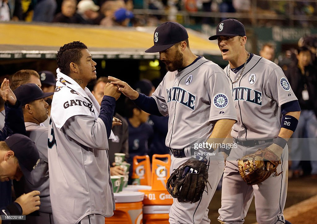 <a gi-track='captionPersonalityLinkClicked' href=/galleries/search?phrase=Felix+Hernandez&family=editorial&specificpeople=550749 ng-click='$event.stopPropagation()'>Felix Hernandez</a> #34 (L) and <a gi-track='captionPersonalityLinkClicked' href=/galleries/search?phrase=Brendan+Ryan&family=editorial&specificpeople=835643 ng-click='$event.stopPropagation()'>Brendan Ryan</a> #26 of the Seattle Mariners congratulates <a gi-track='captionPersonalityLinkClicked' href=/galleries/search?phrase=Dustin+Ackley&family=editorial&specificpeople=4352278 ng-click='$event.stopPropagation()'>Dustin Ackley</a> #13 of the Seattle Mariners after Ackley threw out Coco Crisp #4 of the Oakland Athletics at second base to end the eighth inning during Opening Day at O.co Coliseum on April 1, 2013 in Oakland, California. Hernandez was taken out of the game earlier in the inning and the bases were loaded when Ackley made the play at second base.