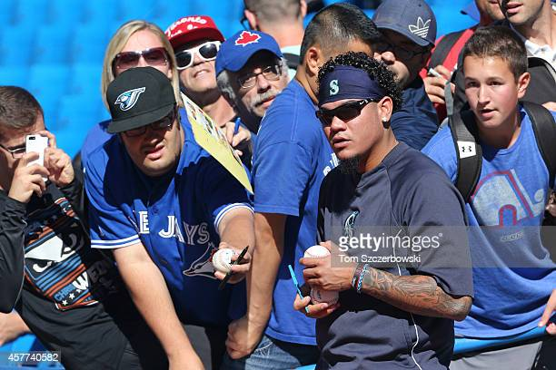 Felix Hernandez of the Seattle Mariners signs autographs for fans during batting practice before the start of MLB game action against the Toronto...