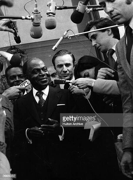 Felix HouphouetBoigny President of the Republic of the Ivory Coast relaxed and smiling as he faces a battery of reporters and microphones on leaving...