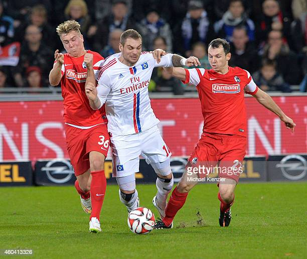 Felix Klaus and Nicolas Hoefler of Freiburg challenges PierreMichel Lasogga of Hamburger SV during the Bundesliga match between SC Freiburg and...