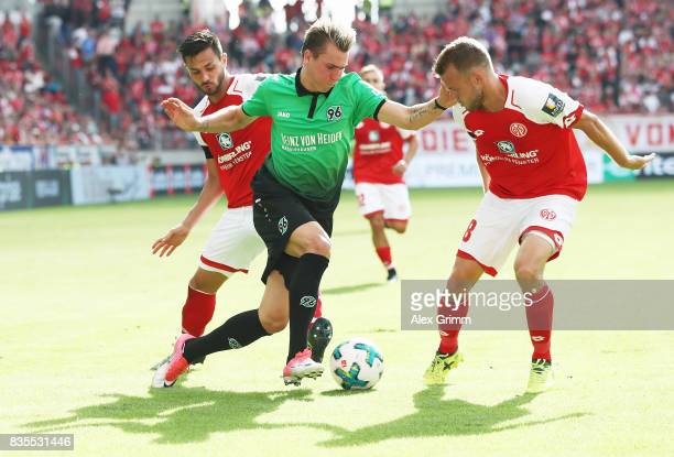 Felix Klaus of Hannover is challenged by Daniel Brosinski and Danny Latza of Mainz during the Bundesliga match between 1 FSV Mainz 05 and Hannover 96...